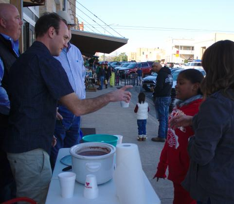 Dan Kleiner at the Elgin Arts Association table hands a cup of hot cocoa to Khaliyah Huerta.