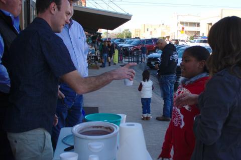 Dan Kleiner at the Elgin Arts Association table hands a cup of hot cocoa to Khaliyah Huerta.